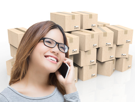 asian woman talking on mobile phone in warehouse with cardboard boxes