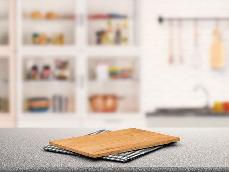cabinetry: chopping board on granite counter top with kitchen cabinet background Stock Photo