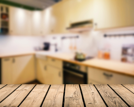 cabinetry: wooden counter top with kitchen blurred background Stock Photo