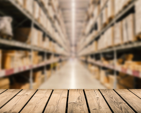 stockroom: wooden counter with warehouse blurred background Stock Photo