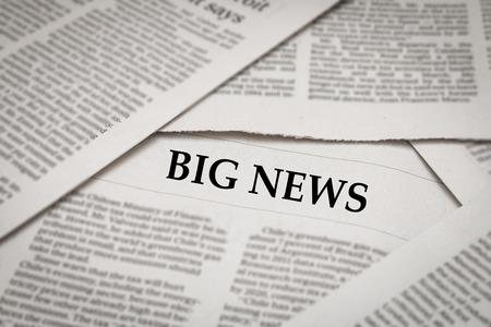 newsfeed: big news headline on newspaper background Stock Photo