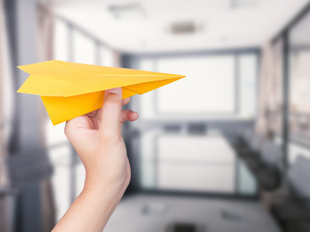 hand holding paper: hand holding paper plane on office background Stock Photo