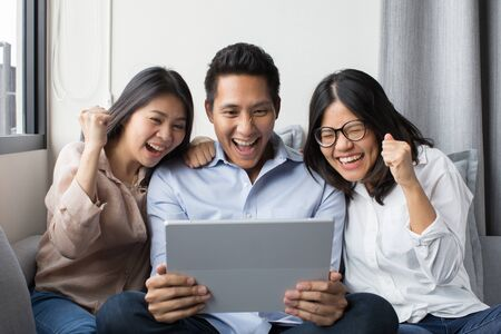 group of colleague looking at digital tablet with happiness
