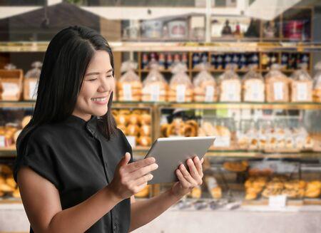 Asian entrepreneur or business owner happy work with digital tablet on bakery shop background