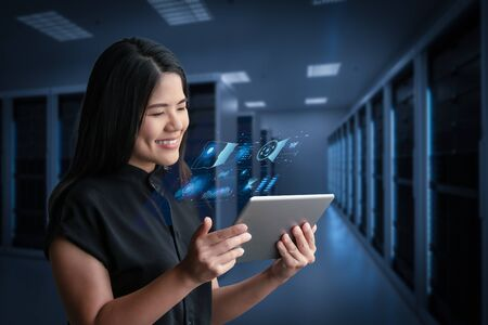 Asian woman smiling with digital tablet in server room Фото со стока