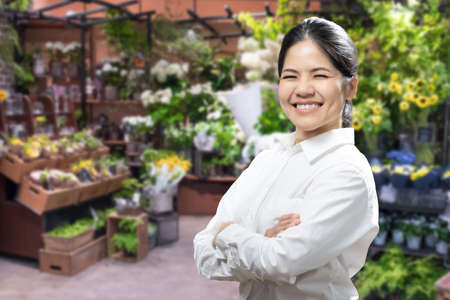 Asian female florist or business owner with florist shop background