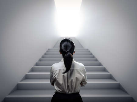 Rear view businesswoman standing at staircase