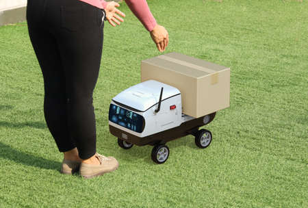 Delivery robot send cardboard box to customer Imagens