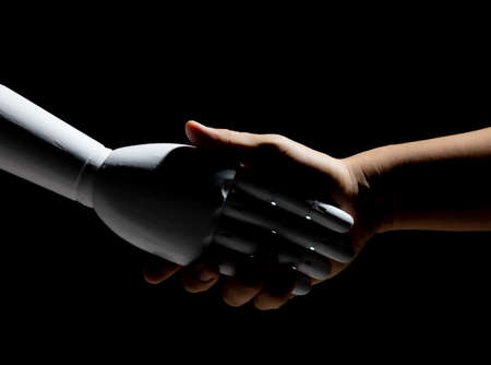 White robot hand shake with human isolated on black background