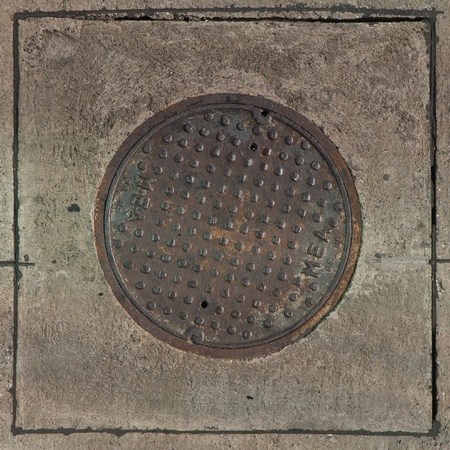 Rustic grunge storm drain manhole cover in concrete Stock Photo - 13067832