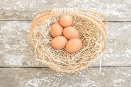 Chicken eggs in a wicker basket near dry grass on the wooden floor photo