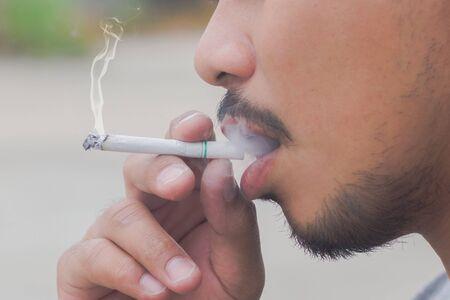hombre fumando: hombre fumando un cigarrillo