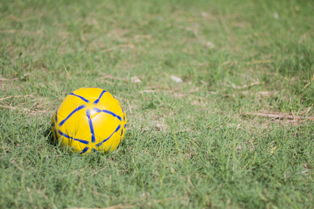 Yellow and blue football on green grass