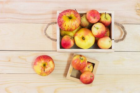 Fresh Apples in a wooden crate on wooden table background Stock Photo