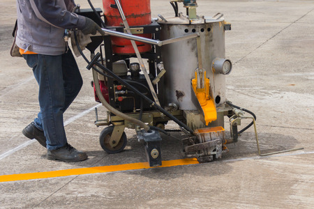 budget repair: Man painting the yellow line on the concrete floor at car park