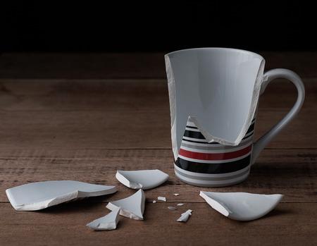 broken cup on wooden background Banco de Imagens