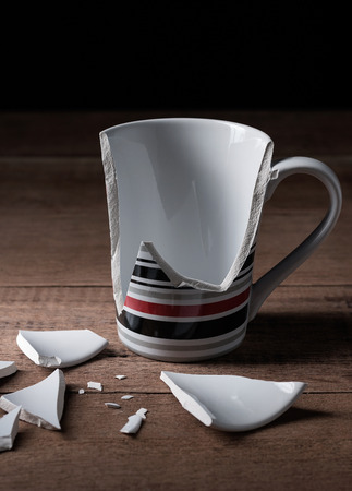 unnecessary: broken cup on wooden background Stock Photo