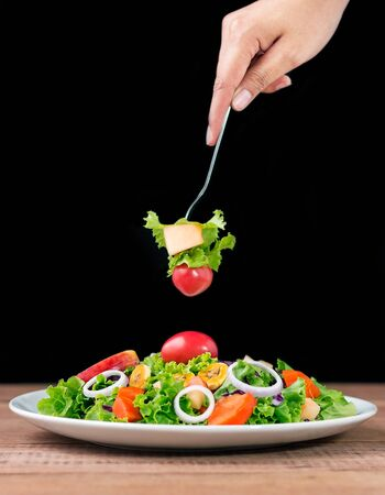Close-up of hands with fork tasting salad
