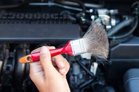 Hand holding brush for cleaning car engine.