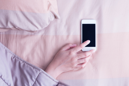Woman hand under blanket being woken by mobile phone in bedroom. Banco de Imagens