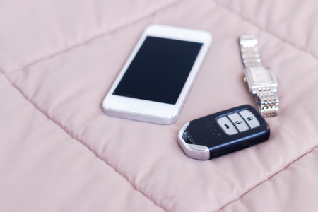 Car key remote, watch and mobile phone on blanket in bedroom.