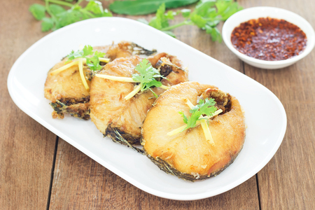 Fried fish with chili sauce on a white plate, Wooden background Stock Photo