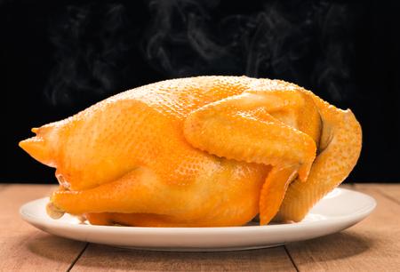 木製のテーブルの上に鶏肉を丸ごと焼き上げた、中華料理