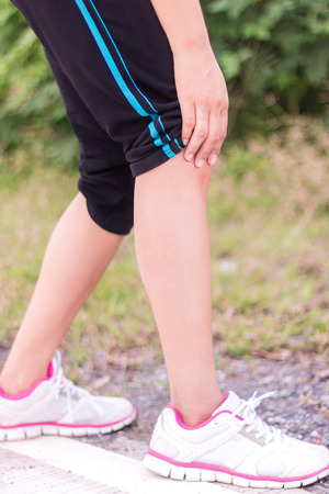 Young woman runner knee injury and pain.
