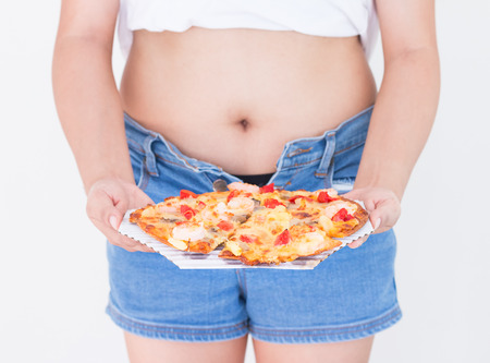 Woman holding pizza with Jeans too tight on belly fat and paunch, Diet concept, Weight lose concept.