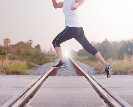 Young woman jumping above the railway during the jogging, Healthy lifestyle and sport concepts.