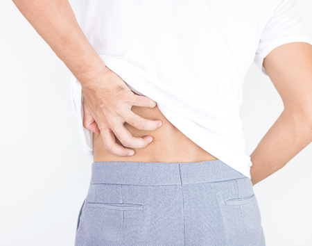 Portrait of young man touching him back with pained expression, suffering from backache after long working hours, Healthy concept. Stock Photo