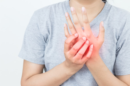 Young woman massaging her painful hand, suffering from hand pain isolated on a white background Banco de Imagens - 102960070