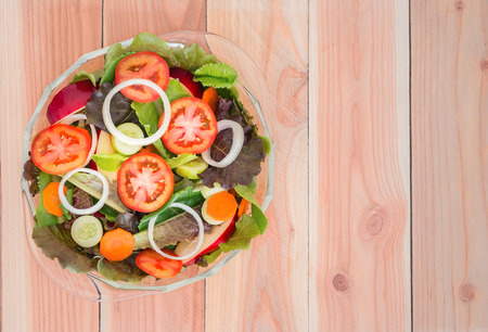 Fresh mixed vegetables salad with tomatoes, apple and lettuce in a bowl on wooden background, Top view