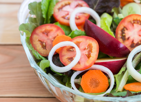 Fresh mixed vegetables salad with tomatoes, apple and lettuce in a bowl on wooden background, Top view Banco de Imagens - 110615299