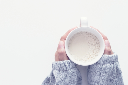 Top view of female hands holding cups of milk on white table background.