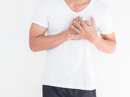 Young man has chest pain, heart attack, hands pressing on chest. Banco de Imagens - 110615309