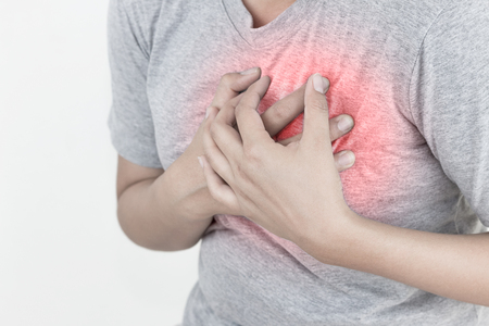 Young woman has chest pain, heart attack, hands pressing on chest.