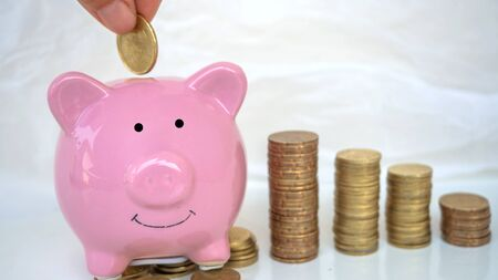 hand putting money in to piggy bank and stake coins in white background. saving money for investment. copy space