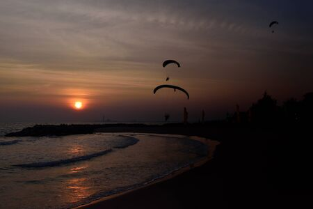 Paramotor flying and sunset on the beach  photo