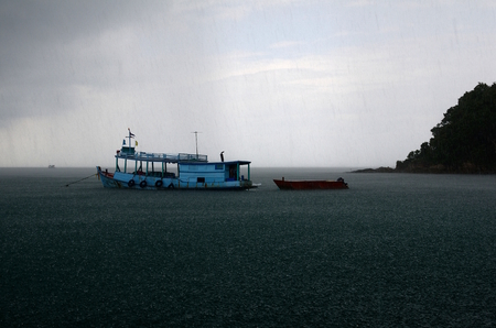 Landscape photo of raining over boat at the sea Stock Photo
