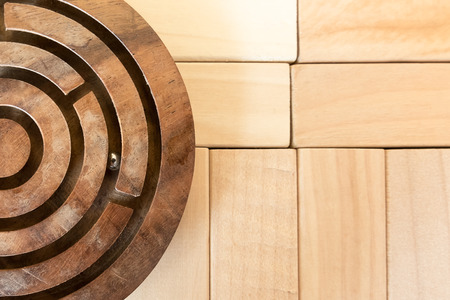 complex system: Circular maze on the wood puzzle background Stock Photo