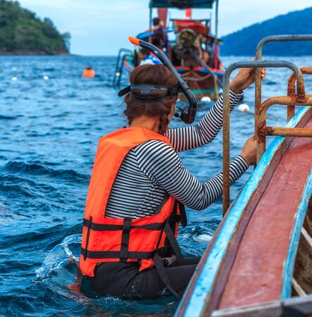 Young woman preparing to snorkel dive with life jacket