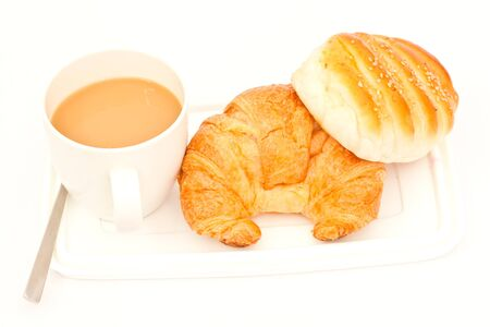 Delicious breads and cup of coffee on white paper photo
