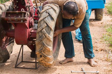 carretilla de mano: agriculturist change wheel of pushcart Foto de archivo