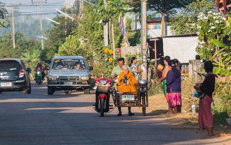 khamin: KALASIN, THAILAND - DEC 13 : Buddhist monk alms round in the moning on December 13,2016 in Ban Khamin, Kalasin Province, Thailand. Editorial