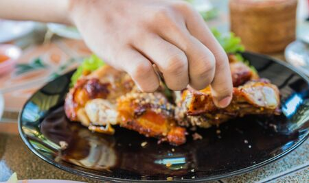 hand with grilled chicken Stock Photo