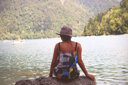 A girl in a colorful dress sits on the shore of the lake to us with her back. On the horizon you can see the water with mountains