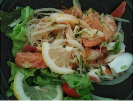 A spicy seafood salad consisting of salmon, squid, lemon, lemon, tomato and green leafy vegetables.