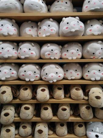 Cute animal dolls on orderly shelves in gift shop background Imagens