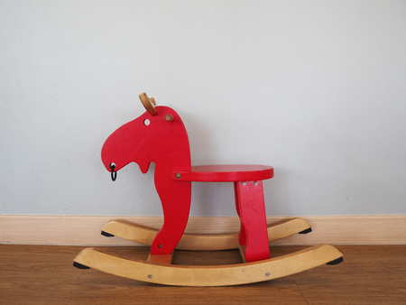 wean: Red rocking horse on wooden floor.